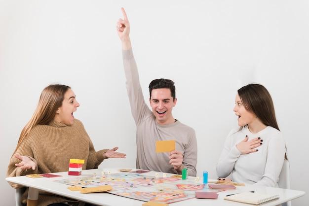 Vue de face des amis surpris en train de jouer à un jeu de société Photo gratuit
