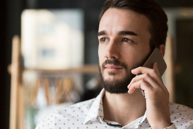 Vue De Face Bel Homme Parlant Au Téléphone Photo gratuit