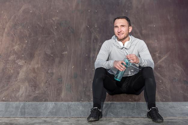 Vue de face bel homme tenant une bouteille d'eau Photo gratuit