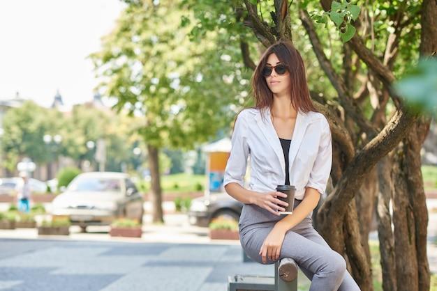 Vue de face de la belle jeune étudiante assise sur un banc en bois. Photo Premium