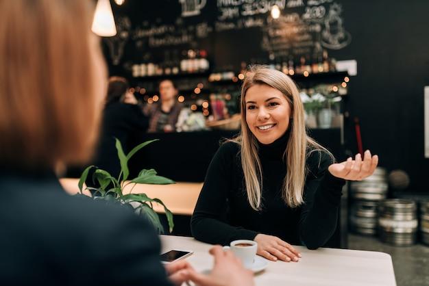 Vue de face de la belle jeune femme parlant à un ami au café. Photo Premium