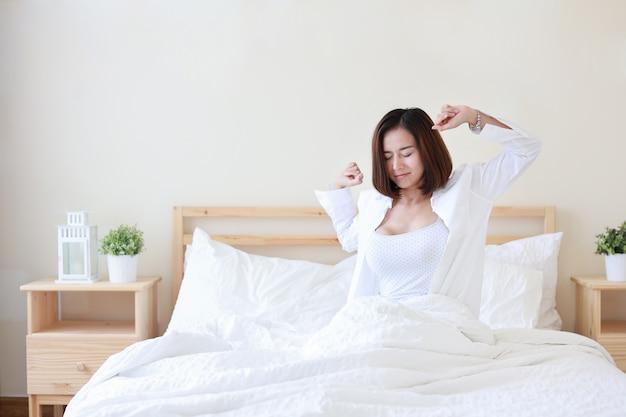 Vue de face belle et saine jeune femme asiatique se réveiller le matin Photo Premium