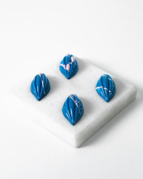 Vue De Face Bleu Pierres Brillantes Isolées Sur L'éponge Blanche Et Le Sol Photo gratuit