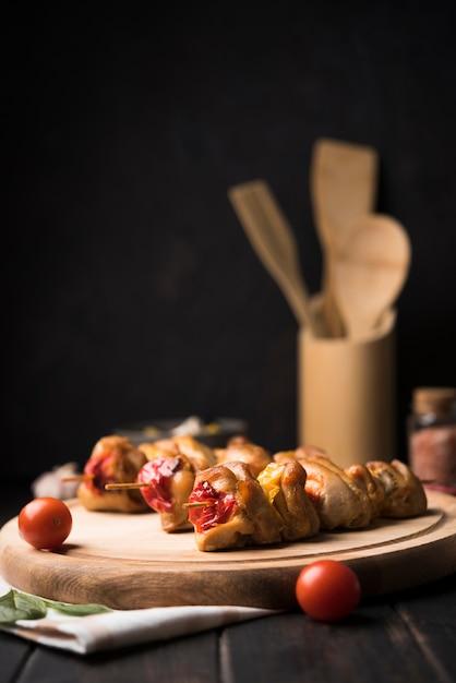 Vue De Face Brochettes Sur Planche De Bois Avec Tomates Photo gratuit