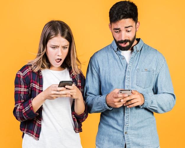 Vue de face choqué couple sur leurs téléphones Photo gratuit