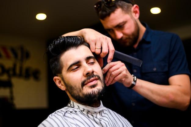 Vue de face coiffeur couper les cheveux du client Photo gratuit