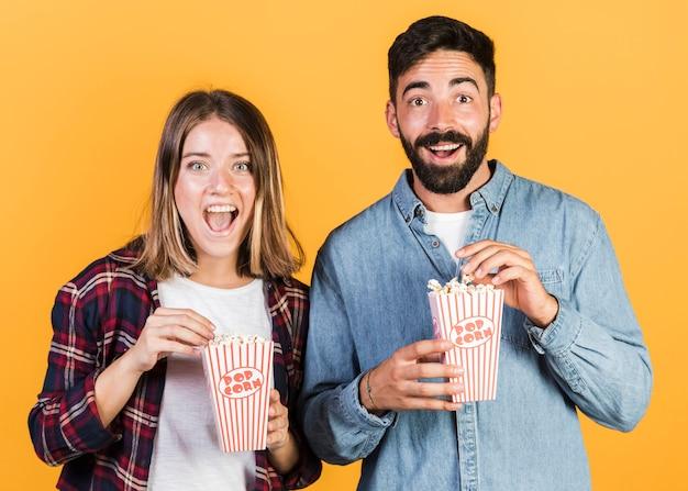 Vue de face, couple heureux avec pop-corn Photo gratuit