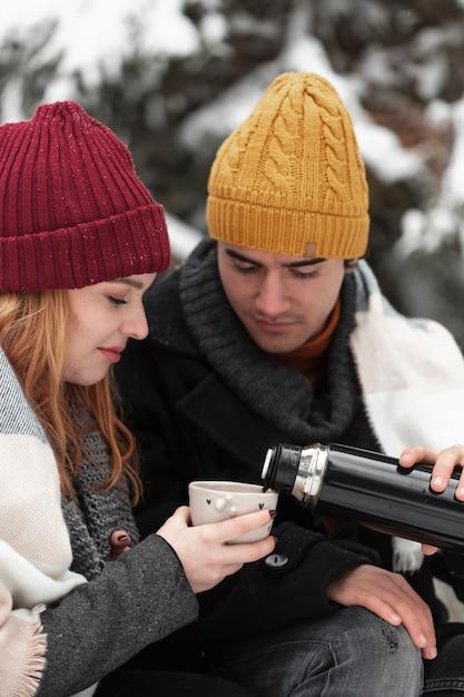 Vue De Face Couple Avec Des Vêtements D'hiver Verser Des Boissons Chaudes Photo gratuit