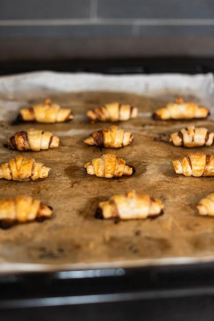 Vue de face des croissants sur une plaque à pâtisserie Photo gratuit
