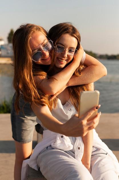 Vue De Face De Deux Femmes Prenant Un Selfie Au Bord Du Lac Photo gratuit
