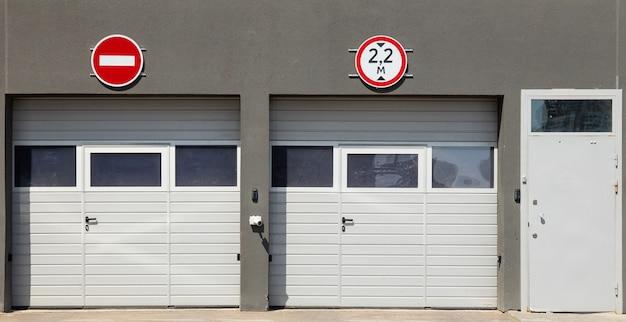 Vue de face à deux portes de garage blanches fermées et une porte d'entrée, murs de moulures grises et panneaux de signalisation dessus Photo Premium