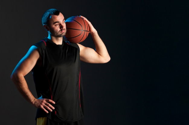 Vue De Face Du Basketteur Avec Ballon Sur L'épaule Et Copie Espace Photo gratuit