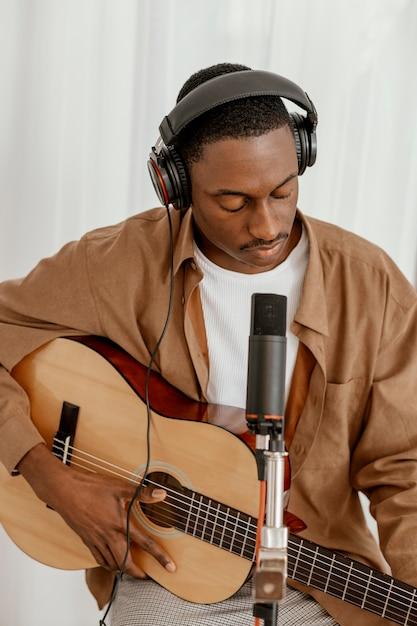 Vue De Face Du Beau Musicien Masculin à La Maison à Jouer De La Guitare Photo gratuit