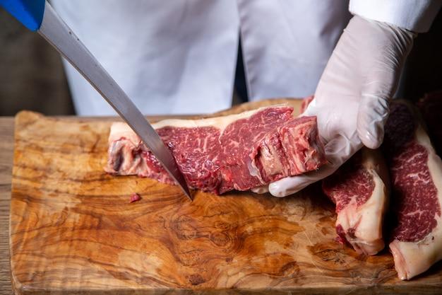 Vue De Face Du Boucher Couper La Viande Dans Des Gants Blancs Tenant Un Gros Couteau Sur Le Bureau En Bois Photo gratuit
