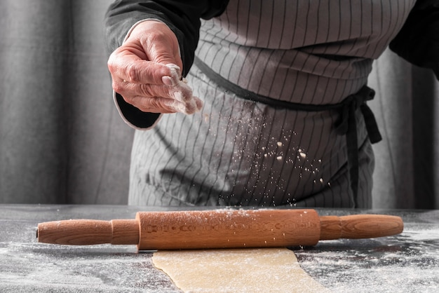 Vue De Face Du Chef Féminin à L'aide De Farine Pour Rouler La Pâte Photo gratuit