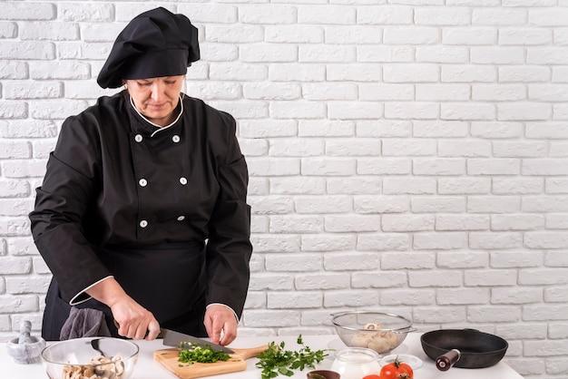 Vue De Face Du Chef Féminin Hacher Les Verts Photo gratuit