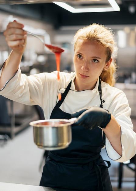 Vue De Face Du Chef Féminin Préparant La Sauce Photo gratuit
