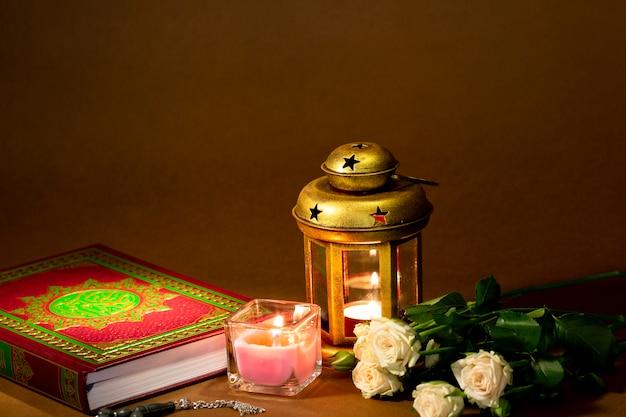 Vue de face du coran avec des bougies et des roses Photo gratuit