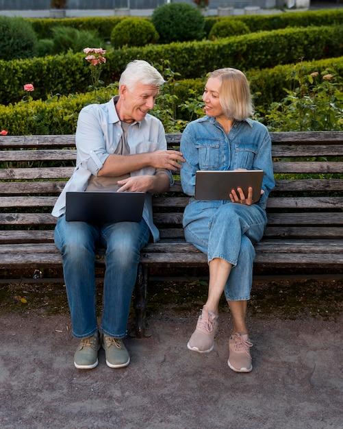 Vue De Face Du Couple Sur Un Banc à L'extérieur Avec Ordinateur Portable Et Tablette Photo Premium