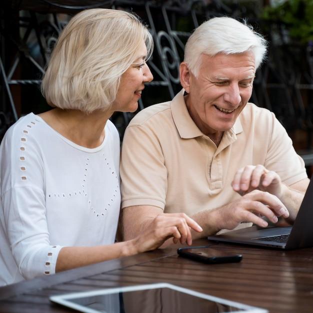 Vue De Face Du Couple De Personnes âgées Dans La Ville Avec Ordinateur Portable Et Tablette Photo gratuit