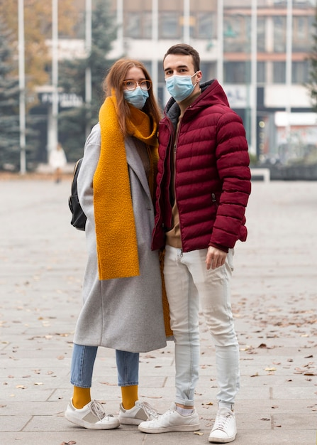 Vue De Face Du Couple Portant Des Masques Médicaux Photo gratuit