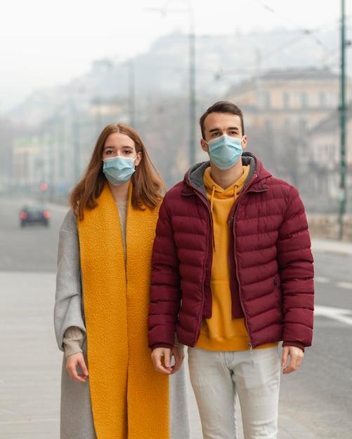 Vue De Face Du Couple Posant Avec Des Masques Médicaux Photo gratuit