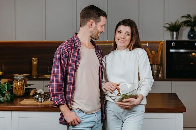 Vue De Face Du Couple Préparant La Nourriture à La Maison Photo gratuit