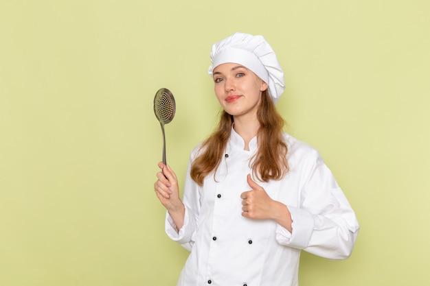 Vue De Face Du Cuisinier Portant Un Costume De Cuisinier Blanc Tenant Une Grande Cuillère En Argent Sur Le Mur Vert Photo gratuit