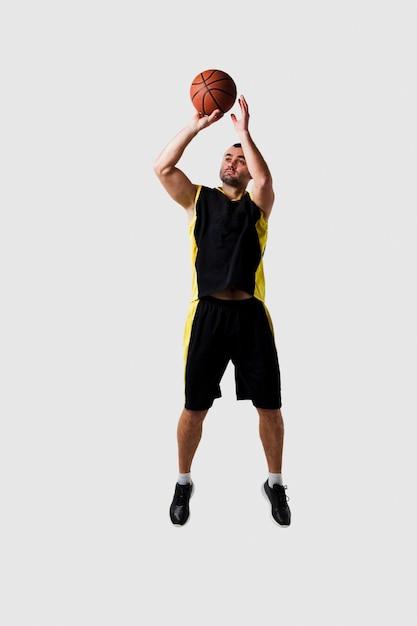 Vue De Face Du Joueur De Basket-ball Posant En L'air Tout En Lançant La Balle Photo gratuit