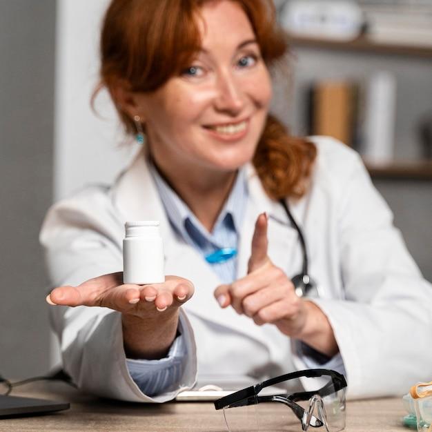 Vue De Face Du Médecin Féminin Souriant Offrant Une Bouteille De Médicament Photo gratuit
