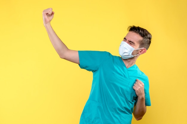 Vue De Face Du Médecin De Sexe Masculin Avec Masque Stérile Sur Mur Jaune Photo gratuit
