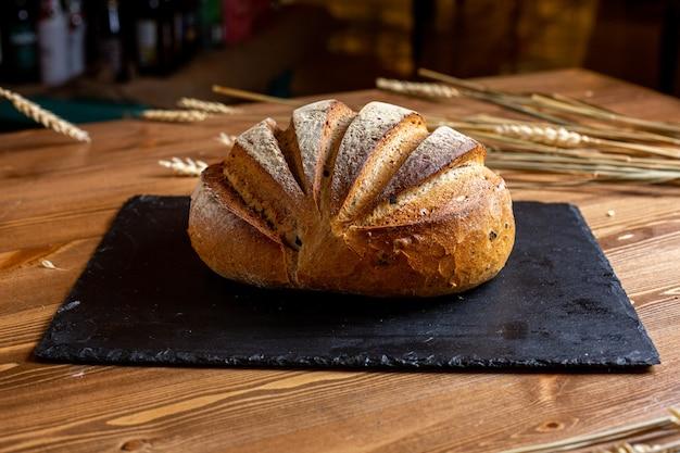 Une Vue De Face Du Pain Blanc Entier Boulangerie Cuit Au Four L'appétit Savoureux Sur Le Tissu Noir Pâte Pâtissière Isolée Photo gratuit
