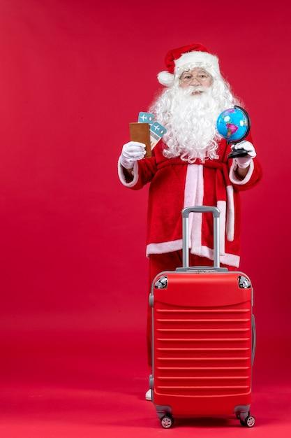 Vue De Face Du Père Noël Avec Sac Tenant Des Billets Et Se Préparant Pour Le Voyage Sur Le Mur Rouge Photo gratuit