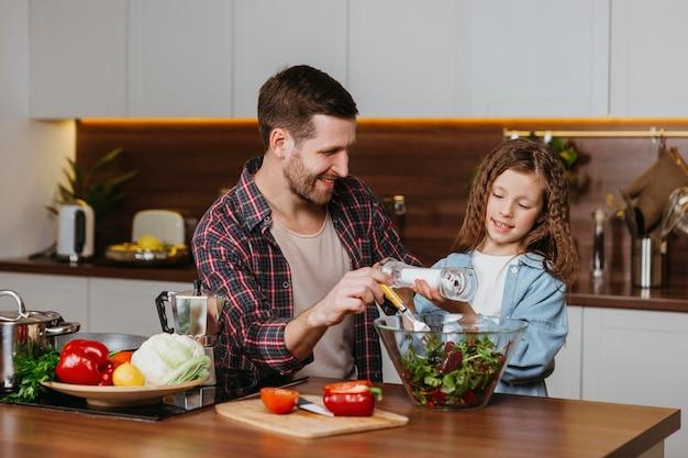 Vue De Face Du Père Souriant Avec Sa Fille, Préparer La Nourriture Dans La Cuisine Photo gratuit