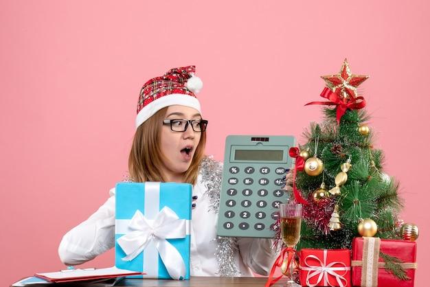 Vue De Face Du Travailleur Féminin Tenant La Calculatrice Autour De Cadeaux Sur Rose Photo gratuit