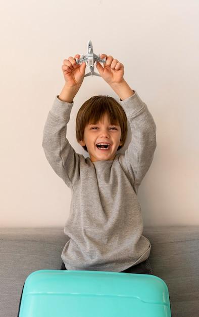 Vue De Face De L'enfant Smiley Avec Bagages Et Figurine D'avion Photo gratuit