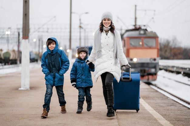 Vue De Face Enfants Et Femme à La Gare Photo gratuit