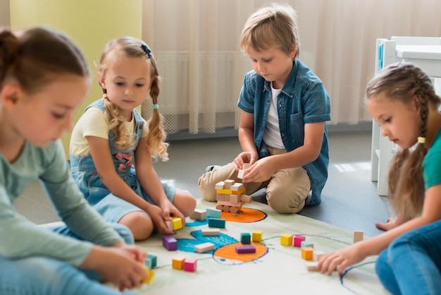 Vue De Face Des Enfants Jouant Ensemble à La Maternelle Photo gratuit
