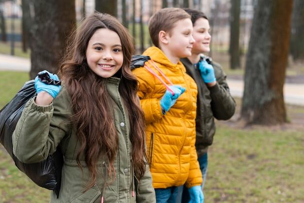 Vue De Face D'enfants Souriants Portant Des Sacs En Plastique Photo gratuit