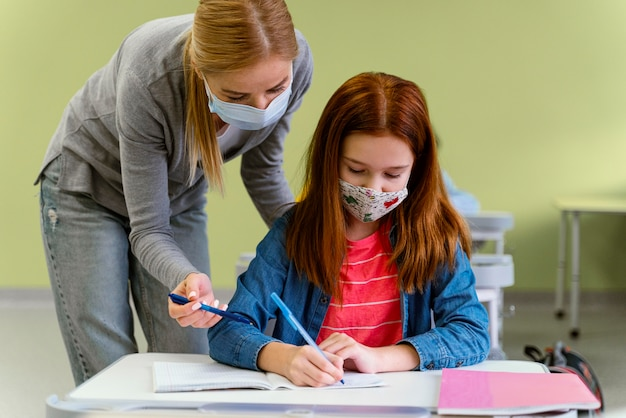 Vue De Face De L'enseignante Avec Masque Médical Aidant La Petite Fille En Classe Photo gratuit