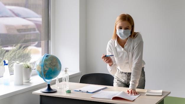 Vue De Face De L'enseignante Avec Masque Médical Au Bureau En Classe Photo Premium