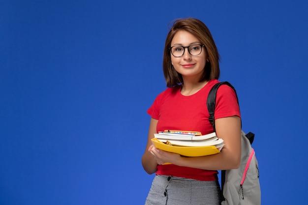 Vue De Face De L'étudiante En Chemise Rouge Avec Sac à Dos Tenant Des Livres Et Des Fichiers Souriant Sur Mur Bleu Photo gratuit