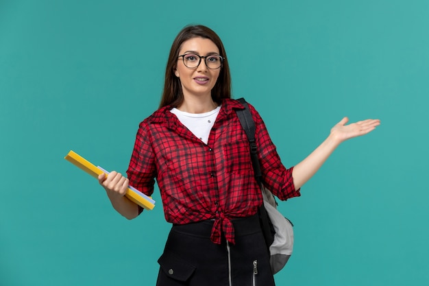 Vue De Face De L'étudiante Portant Sac à Dos Et Tenant Des Fichiers Sur Le Mur Bleu Clair Photo gratuit