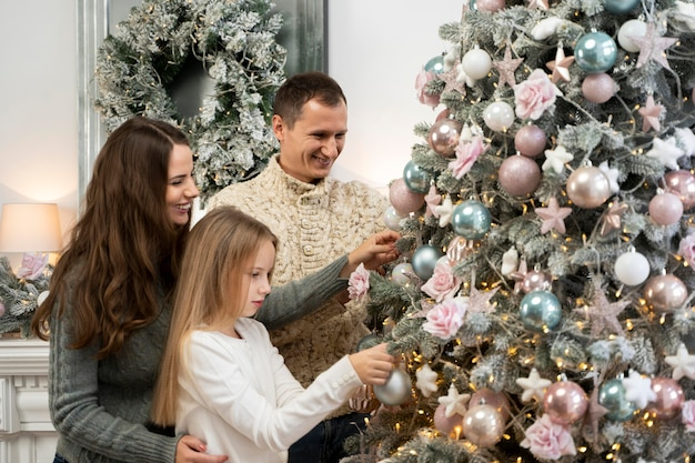 Vue De Face De La Famille Et De L'arbre De Noël Photo gratuit