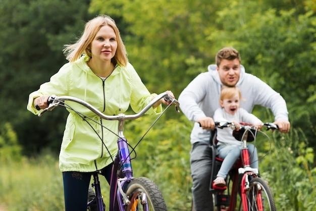 Vue de face de la famille ayant du bon temps avec des vélos Photo gratuit