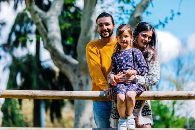 Vue De Face D'une Famille Heureuse Dans Le Parc. Père Mère Et Fils Ensemble Dans La Nature Photo Premium