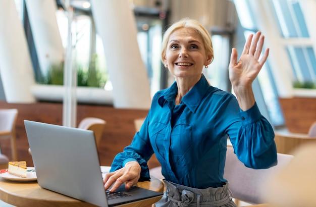 Vue De Face D'une Femme D'affaires Plus âgée Demandant La Facture Tout En Travaillant Sur Un Ordinateur Portable Photo gratuit