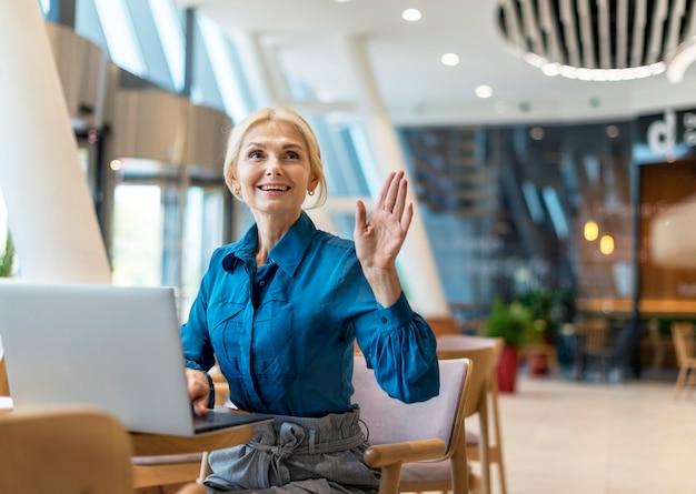 Vue De Face D'une Femme D'affaires Plus âgée Smiley Demandant La Facture Tout En Travaillant Sur Un Ordinateur Portable Photo gratuit