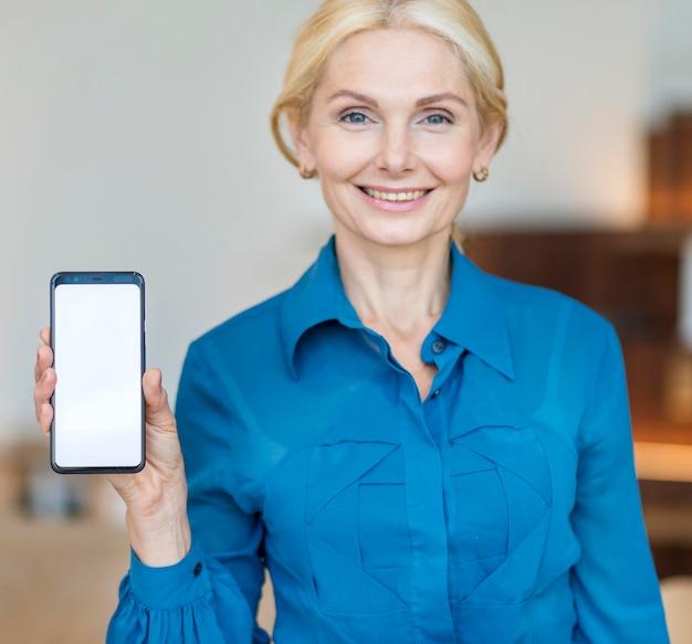 Vue De Face D'une Femme D'affaires Plus âgée Tenant Un Smartphone Photo gratuit