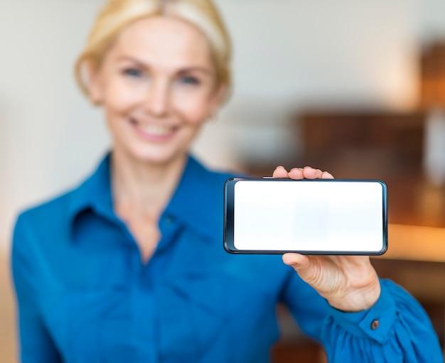 Vue De Face De La Femme D'affaires Smiley Défocalisé Tenant Le Smartphone Photo gratuit